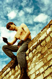 Apocalyptic view. A man sitting on the wall and looks at his hand Stock Photography