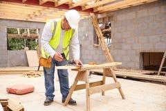 Apoios de Cutting House Roof do carpinteiro no terreno de construção Fotografia de Stock Royalty Free