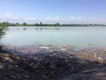 Apokalyptischer Überlebender des Postens in der Gasmaske Die Verschmutzung des Sees, der Teich Die Ansammlung von Plastikflaschen Stockbild