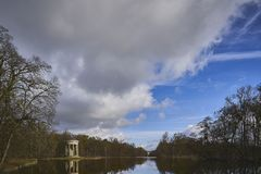 Apollos tempel reflekterade i sjön och i avståndet den Nymphenburg slotten fotografering för bildbyråer