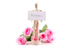 Apologizing Wooden Doll. Apologizing Wooden Art Doll With Flowers Royalty Free Stock Image