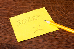 Apology. Note with apology with yellow pencil Stock Image