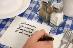 Apology on a napkin. Man's hand scribbles a note of apology on a napkin Royalty Free Stock Photos