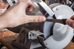 Apontador e mão de faca com a lâmina na tabela de madeira, close up foto de stock
