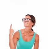 Apontando a mulher moreno com camiseta de alças verde imagens de stock