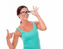 Apontando a mulher moreno com camiseta de alças verde Fotos de Stock