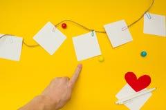 Apontando o dedo em um pedaço de papel, lugar para o texto, fundo amarelo foto de stock