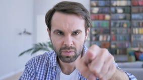 Apontando o gesto pelo homem ocasional da barba, selecionando com alvo do dedo filme
