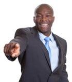 Apontando o homem de negócios africano em um terno escuro Foto de Stock