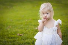 Apontando o vestido branco vestindo da menina em um campo de grama Fotos de Stock Royalty Free