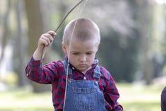 Apontar ativo do menino de madeira cola acima ao andar no parque da mola, menino da crian?a que tem o divertimento que joga a ati imagens de stock