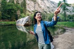Apontar excitado do caminhante mulher alegre ao céu fotografia de stock