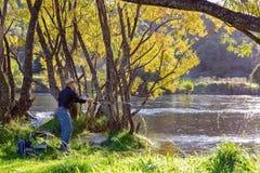 Aposentado que aprecia a pesca no rio bonito fotos de stock royalty free