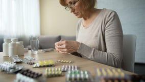Aposente-se o pacote dos comprimidos da abertura da mulher e a instrução da leitura, doença da hipertensão video estoque