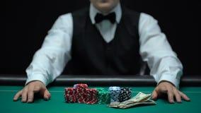 Aposta de espera, microplaquetas e dinheiro do negociante do casino encontrando-se na tabela, negócio de jogo filme
