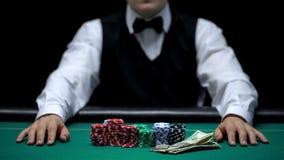 Aposta de espera, microplaquetas e dinheiro do negociante do casino encontrando-se na tabela, negócio de jogo foto de stock