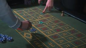 Apostar lasca - os povos da roleta do casino que jogam a roleta Mãos do close-up somente vídeos de arquivo