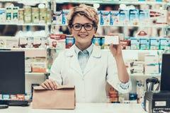 Apotekare Holding Credit Card och påse av medicin arkivbilder