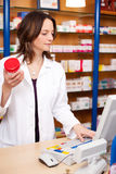 Apotekare Holding Pill Bottle, medan genom att använda datoren på räknaren Royaltyfri Foto