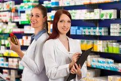 Apotekare med assistenten i apotek Arkivfoton