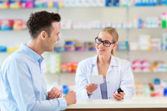 Apotekare och klient på apotek arkivbilder
