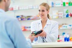 Apotekare och klient på apotek Arkivfoto