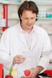 Apotekare Reading Prescription Paper, medan rymma medicinBot Fotografering för Bildbyråer