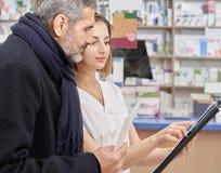 Apotekare som arbetar i apotek med kunder royaltyfria bilder