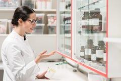 Apotekare som kontrollerar en kemisk farmaceutisk vikt i ett modernt apotek royaltyfri bild