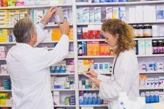 Apotekare som söker mediciner med receptet Arkivfoto