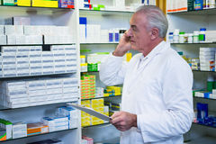 Apotekare som talar på mobiltelefonen, medan kontrollera mediciner fotografering för bildbyråer
