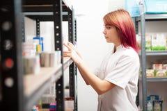 Apotekarekvinna som kontrollerar produkter i lager Arkivbilder
