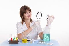 Apotekaren betraktar pulver till och med ett förstoringsglas Royaltyfri Foto