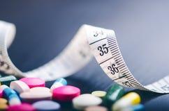 Apotekbakgrund på en svart tabell med att mäta bandet svarta tablets för bakgrund pills Medicin och sunt för kaliberclose för 45  Fotografering för Bildbyråer