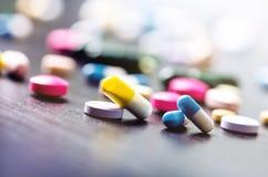 Apotekbakgrund på en svart tabell svarta tablets för bakgrund pills Medicin och sunt kapslar stänger sig upp Differend Arkivbilder
