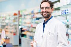 Apothecary в фармации стоя на полке с лекарствами стоковое фото
