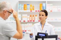 Apothecary давая лекарство к старшему человеку на фармации стоковое фото rf