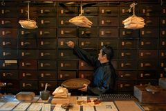 Apothecary. Worker opening drawer to take out main ingredient stock photos