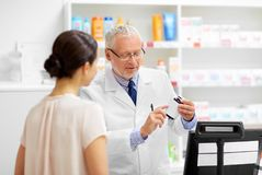 Apothecary with cure and customer at pharmacy. Medicine, pharmaceutics, healthcare and people concept - senior apothecary with drug and female customer at royalty free stock photos