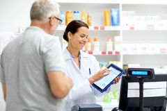 Apothecary and customer with tablet pc at pharmacy. Medicine, healthcare and technology concept - happy apothecary and senior male customer with digital royalty free stock photo