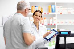 Apothecary and customer with tablet pc at pharmacy. Medicine, healthcare and technology concept - happy apothecary and senior male customer with digital stock photography