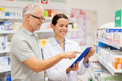 Apothecary and customer with tablet pc at pharmacy. Medicine, pharmaceutics, healthcare and technology concept - happy apothecary and senior customer with tablet Stock Images