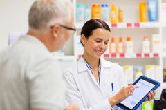 Apothecary and customer with tablet pc at pharmacy. Medicine, pharmaceutics, healthcare and technology concept - happy apothecary and senior customer with tablet royalty free stock image
