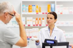 Apothecary giving drug to senior man at pharmacy. Medicine, pharmaceutics, health care and people concept - apothecary giving analgetic drug to senior men royalty free stock photo