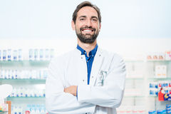 Apothecary in pharmacy standing at shelf with drugs Royalty Free Stock Images