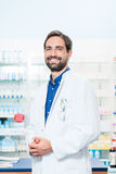 Apothecary in pharmacy standing at shelf with drugs Stock Photos