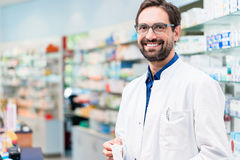 Apothecary in pharmacy standing at shelf with drugs stock photo