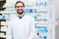 Apothecary in pharmacy standing at shelf with drugs Royalty Free Stock Image
