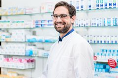 Apothecary in pharmacy standing at shelf with drugs. Smiling Royalty Free Stock Photo