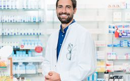 Apothecary in pharmacy standing at shelf with drugs. Apothecary in pharmacy store standing at shelf with drugs Royalty Free Stock Image